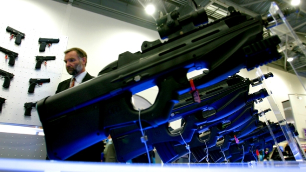 A MAN WALKS PAST A TACTICAL F2000 RIFLE STAND AT THE DSEI EXHIBITION IN LONDON.